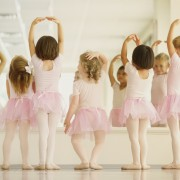 Ballet dancers performing in front of mirror in pink leotards and tutus